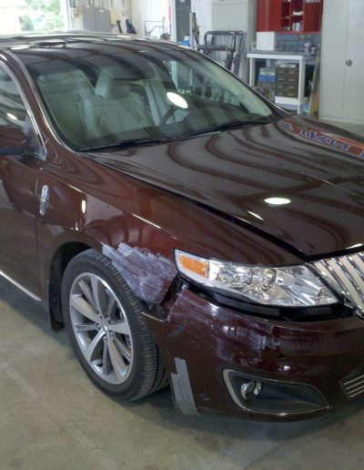 A dark red car undergoing paint repair at Blackburn Collision Center