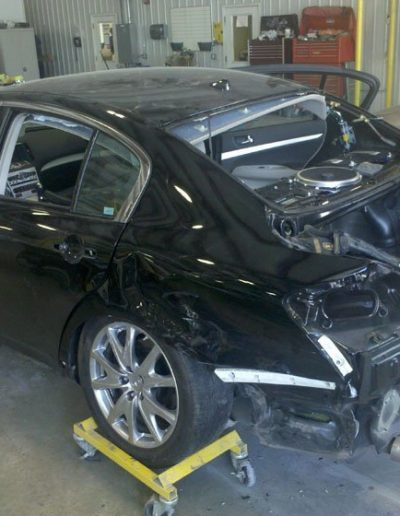 A black car undergoing repair on the back end