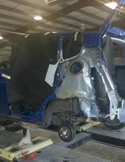 A badly damaged blue van being repaired