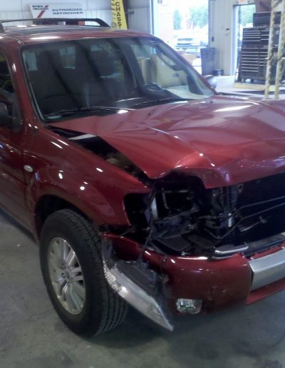 A red SUV with a badly damaged front end
