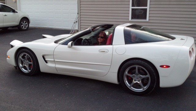 A happy woman in her recently repaired white convertible